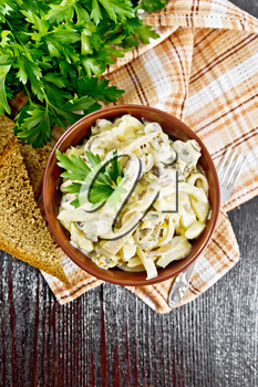 Salad with squid, egg and mushrooms in a bowl on a napkin, bread, fork and parsley on dark wooden board background from above