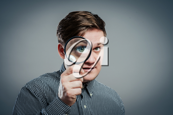 Funny image of a adultman with a magnifying glass, one eye is enlarged.