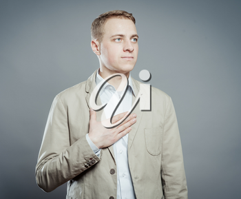 young man with chest pain standing at gray background