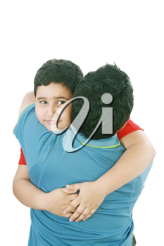 Portrait of a young boy hugging his father against white background