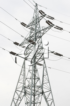 Power transmission tower with cables against the gray sky background