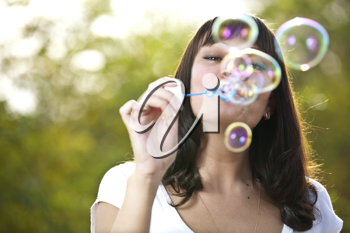 Young beautiful girl blowing bubbles outdoors