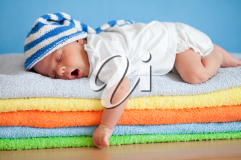 Royalty Free Photo of a Baby Sleeping on a Stack of Towels