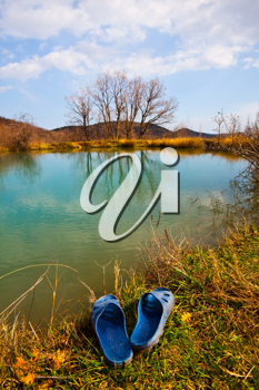 Royalty Free Photo of a Lake and Sandals