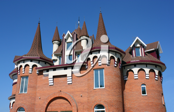 The house with a beautiful roof with windows and carved domes from a red brick.