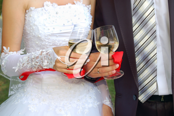 two glasses with champagne in the hands of groom and fiancee