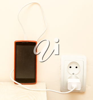cell phone is being charged from the electrical outlet