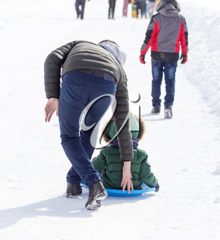 Dad rolls the child on a sled