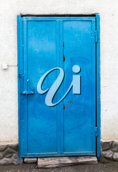 Blue iron door on a concrete wall .