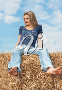 Royalty Free Photo of a Girl Sitting on a Haystack