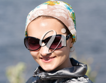 Close-up portrait of beautiful girl in the bandana and sunglasses
