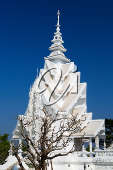 spire of the White Temple in Chiang Mai, Thailand, on a background of blue sky.