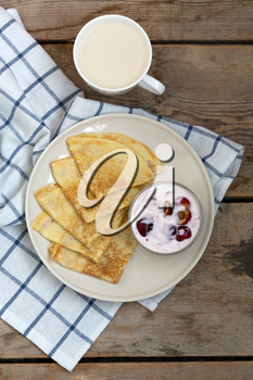 Fried pancakes with jam and a cup of milk on vintage wooden background. Top view