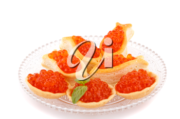 Red caviar in pastries on glass transparent plate.