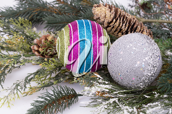 Christmas colorful balls, cones, fir-tree branch on gray background.