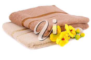 Folded towels and flowers isolated on white background.