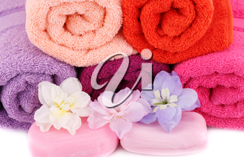 Towels, soaps and flowers closeup picture.