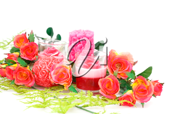 Colorful roses and candles on white background.