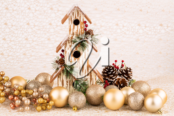Christmas decoration with birdhouse, cones and balls on the golden net.