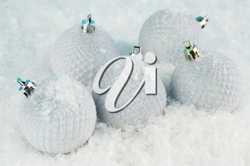 Christmas balls on the artificial snow background.