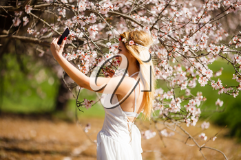 Young beautiful romantic blonde woman in white dress taking a selfie in blooming garden.