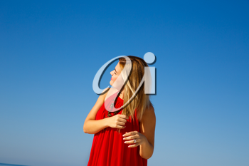 Blond woman in the red dress on the blue sky background.