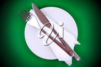 Table serving-knife,plate,fork and silk napkin  on  green colour background.