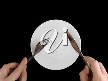 Table serving-knife, fork in hands on colour background.