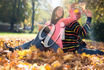 Young Couple With Headphones And Throwing Fall Leaves