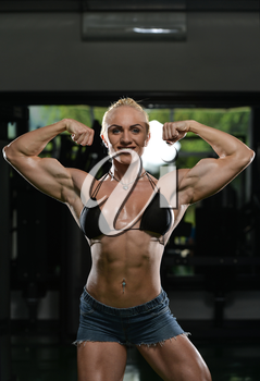 Serious Woman Bodybuilder Standing In The Gym And Flexing Muscles