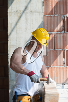 A Handsome Construction Man Using A Hammer To Nail Together Wood