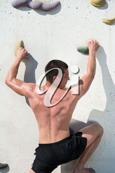 Young Man Climbs Up An Outdoors Rock Wall - He Is Clearly Determined To Make It To The Top