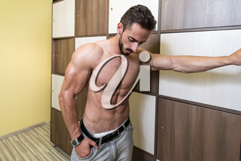 Muscular Build Athlete Changing In Gym's Locker Room And Having A Rest After Workout