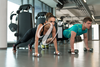 Young Couple Doing Exercise With Dumbbells In The Gym