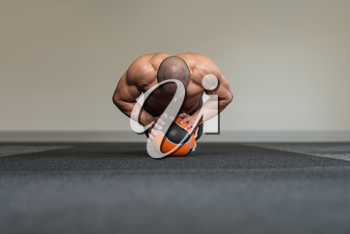 Young Man Exercise With Medical Ball In Fitness Club