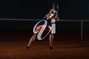Young Female Tennis Player With Racket Ready To Hit A Tennis Ball - Back View