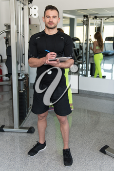 Personal Trainer With Clipboard Monitors People While They Exercise In A Gym Or Fitness Club