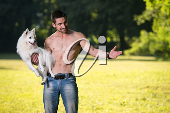 Sexy Young Man Holding Dog German Spitz In Park - Together Enjoying The View