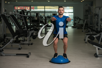 Personal Trainer Doing A Exercise With Bosu Balance Ball As Part Of Bodybuilding Training
