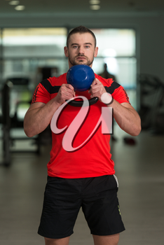 Personal Trainer Working Out With Kettle Bell In A Gym - Attractive Fitness Instructor Doing Heavy Weight Exercise With Kettle-bell