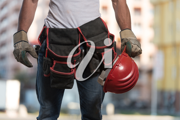 Close Up Of Hard Hat Holding By Construction Worker