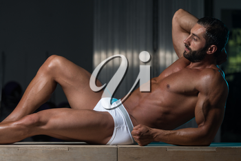 Portrait Of A Sexy Muscular Man In Underwear Resting On Box After Exercise