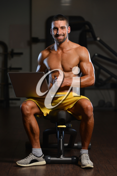Portrait Of A Young Physically Fit Man Using Laptop - Muscular Athletic Bodybuilder Fitness Model Use Computer