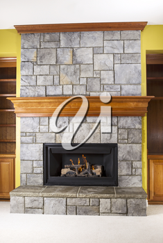 Natural Gas fireplace built with stone and wooden mantels in family room of modern home