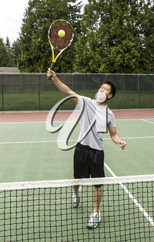 Young Asian Man taking an overhead volley on outdoor tennis court