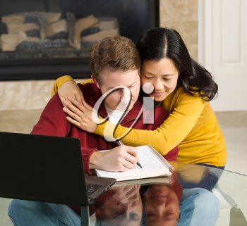 Photo of close mature couple displaying happiness while working from home with fireplace in background