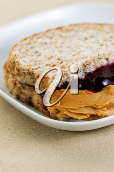 Closeup vertical photo of peanut butter and jelly sandwich, cut in half, inside white plate on textured table cloth underneath
