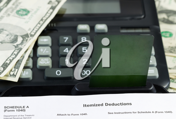 Horizontal photo of a blank credit card inserted in keyboard with partial IRS Income tax form and calculator with cash in background