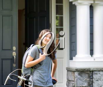 Image of teenage girl, waist up and looking forward, carrying school bag while resting against her bicycle with home in background