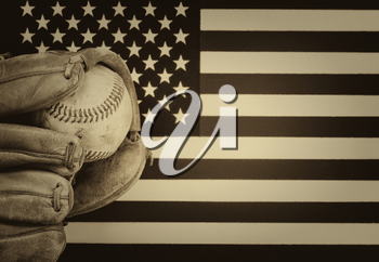 vintage concept of worn leather mitt and used baseball with United States of America flag in background.